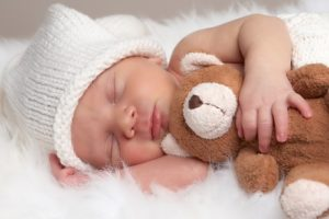 Sleeping Newborn Holding A Teddy Bear